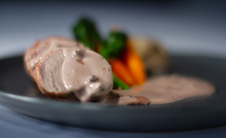 Pork fillet wrapped in pancetta with peppercorn sauce